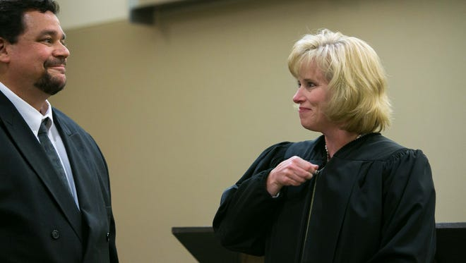 Janell S. Ostroski puts her judicial robe on during a ceremony Friday as husband  Drew Ostroski looks on. Gov. Jack Markell nominated Ostroski to her first term as a Family Court judge earlier this year.