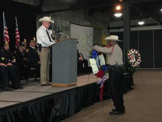 Nueces County Sheriff Jim Kaelin watches as a sheriff's deputy places a flower on a wreath in memory of a fallen deputy. Kaelin recited the names of six fallen deputies during a peace officers memorial at the Congressman Solomon P. Ortiz International Center on May 14, 2018.