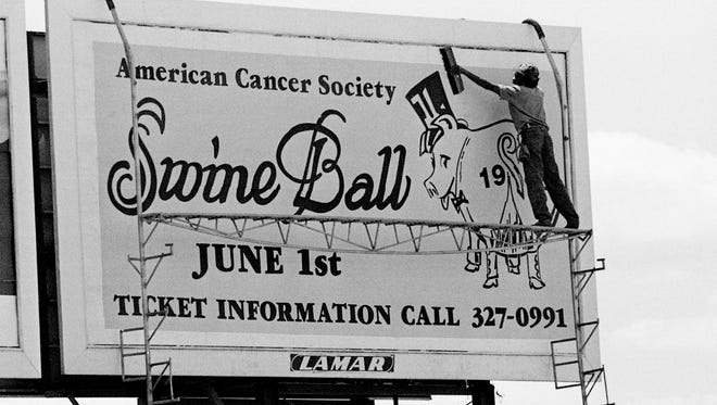 An employee of Lamar Advertising Co. puts the finishing touches on the first of 10 billboards May 15, 1985 that the firm is donating to the annual Swine Ball benefit. The event to benefit the American Cancer Society will be held at the Metro tow-in lot in East Nashville June 1st.