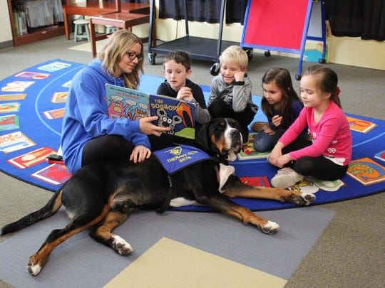 Certified therapy dog Skye listens intently as students in the S.M.I.L.E. program take turns practicing their reading skills.