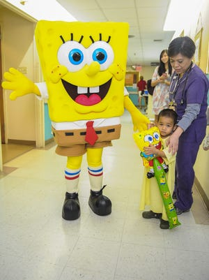 Three-year-old patient Elijah Pangelinan poses for a photo with Nickelodeon's SpongeBob SquarePants during the animated character's visit to the pediatric ward at the Guam Memorial Hospital in Tamuning on Wednesday, Sept. 23. The visit, conducted by Docomo Pacific, was done as part of the company's Kids4Kids Carnival event being held this weekend. The costumed-character was able to visit with 14 children at the ward, children that most likely wouldn't have been able to attend the carnival, said Marissa Borja, Docomo Pacific public relations coordinator. Rick Cruz/Pacific Daily News/rmcruz@guampdn.com