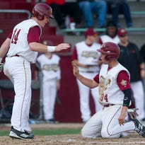 Wisconsin Rapids Rafters' Kyle Devin, left, congratulates Max Widmar, right, after he slid into home base during the Northwoods League baseball game against the Wisconsin Woodchucks at Witter Field in Wisconsin Rapids, Wednesday, May 27, 2015.