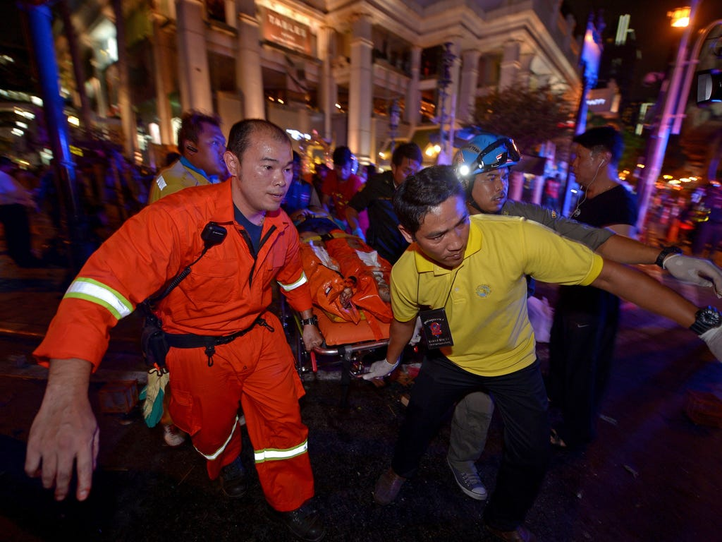 Thai rescue workers carry an injured person after a bomb explodes outside a religious shrine in central Bangkok, killing at least 10 people and wounding scores more.