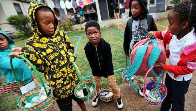 Kids gather in front of Purple House which is part of the Carpenter Art Garden after coloring Easter eggs Tuesday after school. The house and garden host tutoring and small group art lessons for neighborhood kids in the Binghampton area.