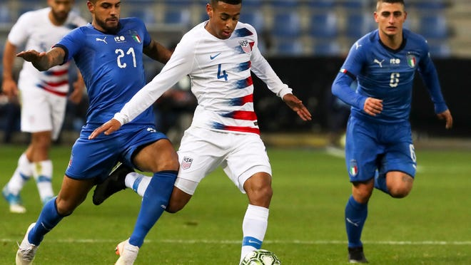 United States' Tyler Adams (4) is pursued by two Italian defenders during an international friendly soccer march on Nov. 18, 2018 in Belgium.