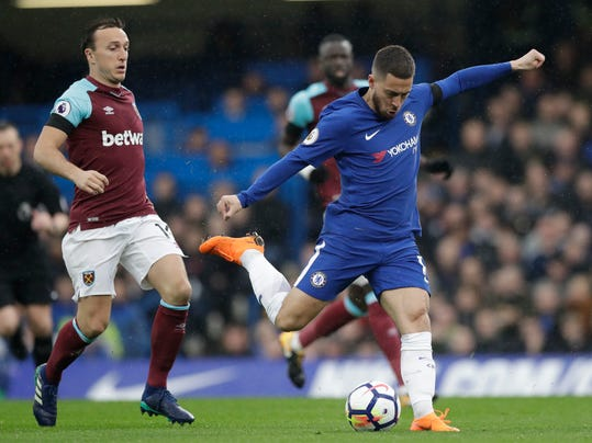 Chelsea's Eden Hazard shoots during the English Premier League soccer match between Chelsea and West Ham United at Stamford Bridge stadium in London, Sunday, April 8, 2018. (AP Photo/Matt Dunham)