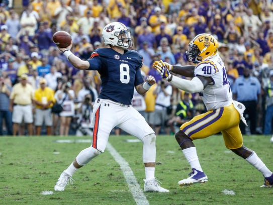 Auburn Tigers quarterback Jarrett Stidham (8) is hit