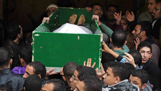 Egyptians carry the coffin of a man killed during Saturday's clashes between protesters and security forces at the Zeinhom morgue in Cairo, Egypt, Sunday, Jan. 26, 2014.