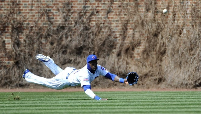 Cubs left fielder Junior Lake (21) tries to make a catch on a RBI double by Reds center fielder Billy Hamilton during the sixth inning at Wrigley Field on Friday.