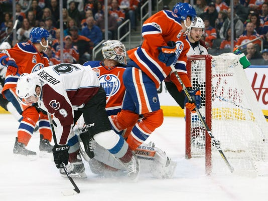 Edmonton Oilers' Ryan Nugent-Hopkins (93) and Colorado Avalanche's Matt Duchene (9) collide in front of Oilers goalie Laurent Brossoit (1) during first-period NHL hockey game action in Edmonton, Alberta, Saturday, March 25, 2017. (Codie McLachlan/The Canadian Press via AP)