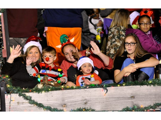 Young and not-so-young parade participants wave from the back of a trailer during the 2017 City Sidewalks Christmas Lights Parade.