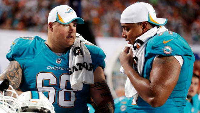 Richie Incognito (68) and  Jonathan Martin (71) talk during a preseason football game last August between the Miami Dolphins and Tampa Bay Buccaneers.