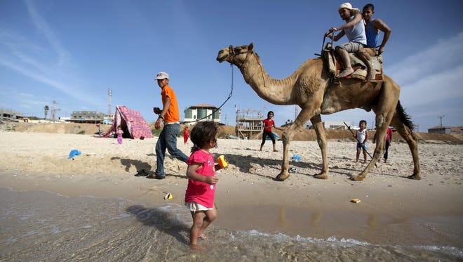 A Palestinian child looks at men riding a camel on the beach in Gaza City, Sunday, May, 4, 2014.