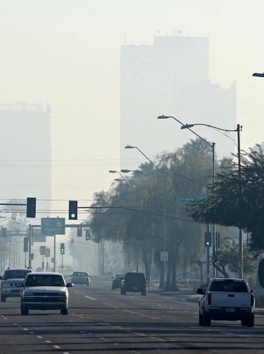 High rises in downtown Phoenix are obscured by smog in this view looking east on Van Buren from 27th Avenue on January 1, 2016
