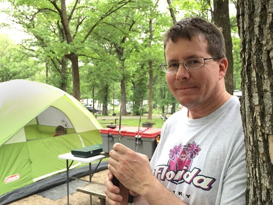 Monty Headley of Sauk Rapids, the Benton County administrator, prepared supper while his son Gregory, 10, occupied the tent during a June outing at Sibley State Park.