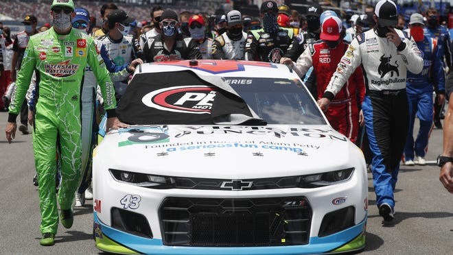 Drivers Kyle Busch, left, and Corey LaJoie, right, join other drivers and crews as they push the car of Bubba Wallace to the front of the field before the start of Monday's race.
