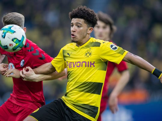 "FILE - In this Jan. 27, 2018 file photo Dortmund's Jadon Sancho, right, and Freiburg's Lukas Kuebler, left, challenge for the ball during the German Bundesliga soccer match between Borussia Dortmund and SC Freiburg in Dortmund, Germany. Sancho has been ruled out for ""several weeks"" with an ankle injury. The Bundesliga club says an MRI examination revealed the 17-year-old Sancho suffered a ligament injury in Friday's league win at Cologne. (Guido Kirchner/dpa via AP, file)"