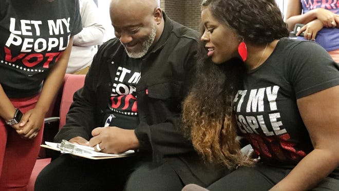 n this Jan. 8, 2019 photo, former felon Desmond Meade and president of the Florida Rights Restoration Coalition, left, fills out a voter registration form as his wife Sheena looks on at the Supervisor of Elections office in Orlando.