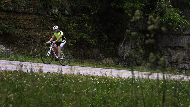 John White makes his way up a hill a he rides his bike along the Natchez Trace Parkway/