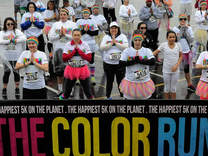 Runners do yoga in the LP Field parking lot before the Color Run, a 5K run that celebrates healthiness, happiness and individuality, on Saturday in Nashville.