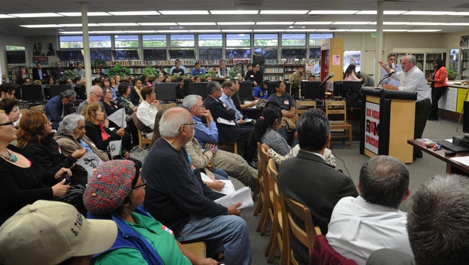 State officials from the Department of Pesticide Regulation speak to a standing room only crowd at the Rio Mesa High School library in June 2015