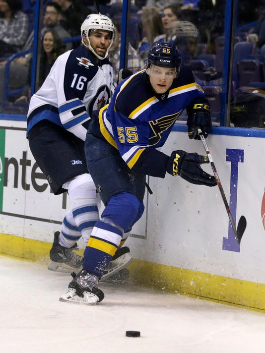 Winnipeg Jets' Andrew Ladd, left, and St. Louis Blues' Colton Parayko chase after a loose puck during the first period of an NHL hockey game Tuesday, Feb. 9, 2016, in St. Louis. (AP Photo/Jeff Roberson)