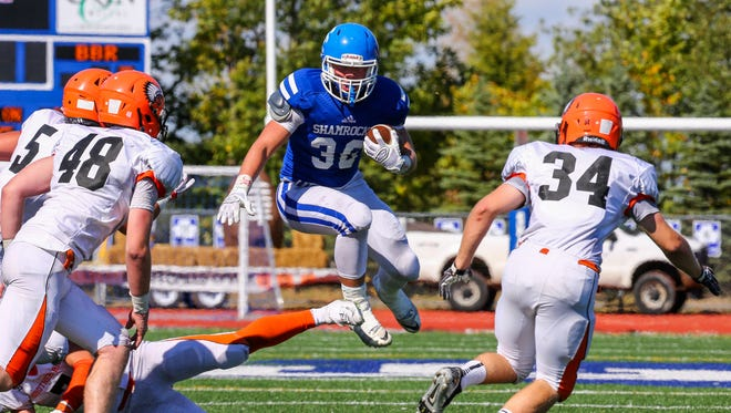Catholic Central running back Cameron Ryan (36) jumps into the hole between Brother Rice tacklers Michael Laurencelle (48) and Timothy Dougherty (34) in Sunday's Boys Bowl.