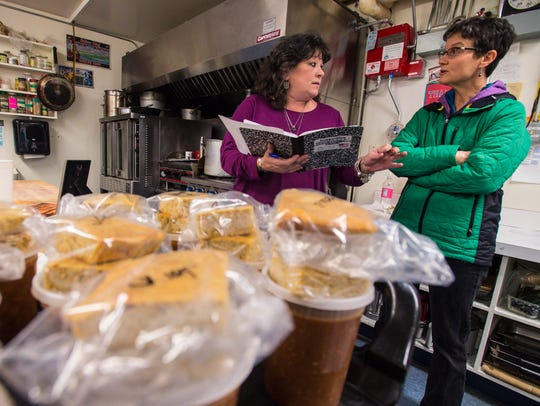 Sandy Heyman, left, goes over a delivery route with