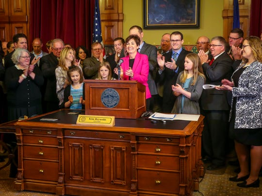 Gov. Kim Reynolds and others applaud  after she signed