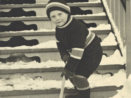 Hugh Wright posing with a hockey stick as a child.