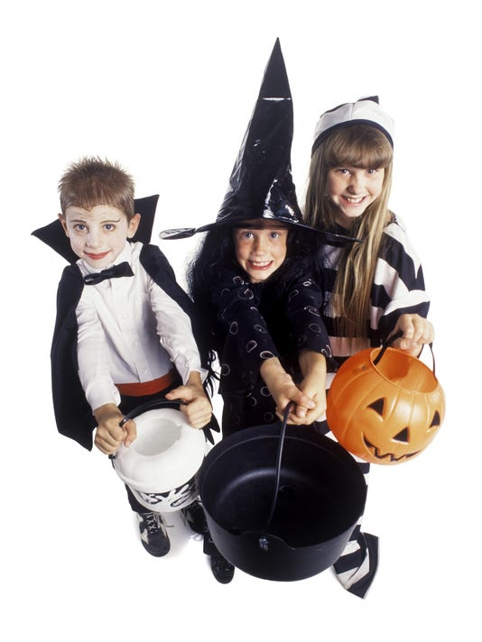 three children dressed for Halloween huddle together holding out candy pails