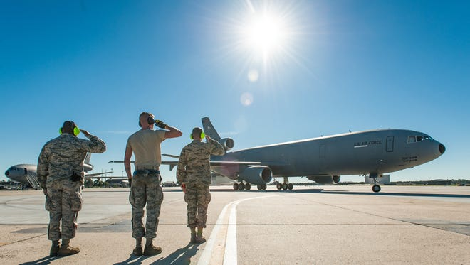 Military personnel at Joint Base McGuire-Dix-Lakehurst offer salutes on the tarmac with a KC-10 tanker plane in this file photo.