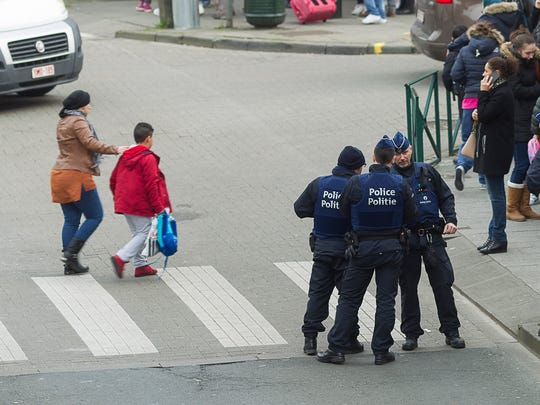 People cross the road as police secure the area in