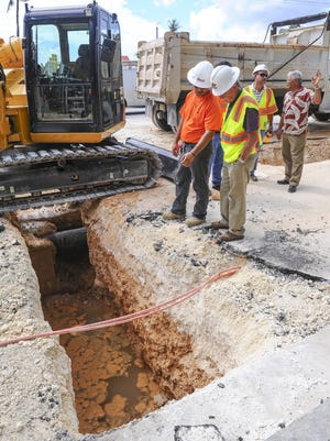 Felix Benavente, far right, Department of Public Works acting director, consults with engineers on options to repairing a section of roadway in East Hagatna on Wednesday, July 22.