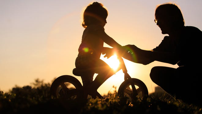 father teaching daughter to ride bike at sunset, active kids sport