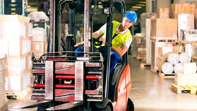 A stock image showing a man operating a forklift in a warehouse.
