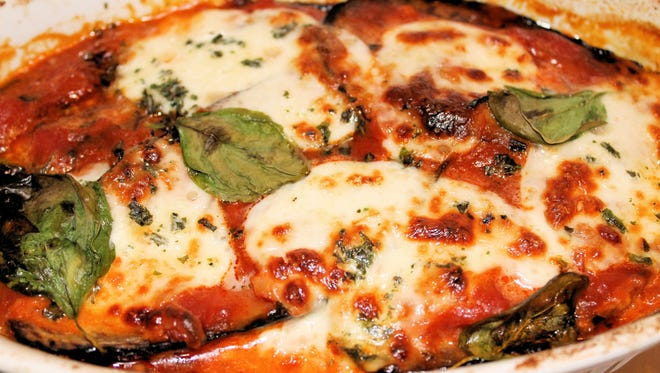 Eggplant parmigiana with tomatoes and cheese has rich flavors for a home entree.