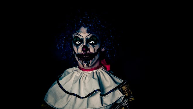 Crazy ugly grunge evil clown in town on Halloween making people shocked and scared