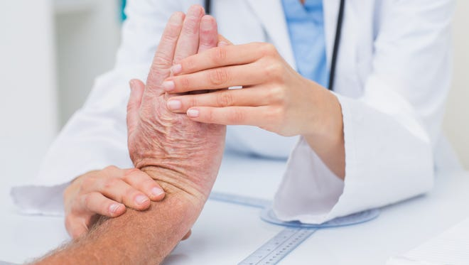 A physiotherapist examining a patients wrist.