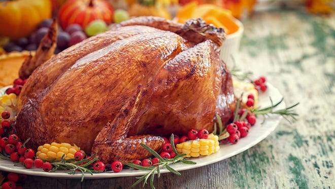 A Thanksgiving turkey dinner with cranberries and corn.