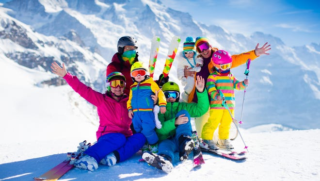 Family ski vacation. Group of skiers. Adults and young children, teenager and baby skiing in winter. Parents teach kids alpine downhill skiing. Ski gear and wear, safe helmets.