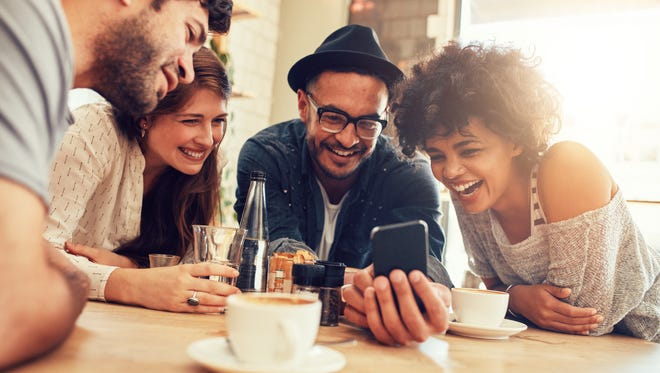 Portrait of cheerful young friends looking at smart phone while sitting in cafe.
