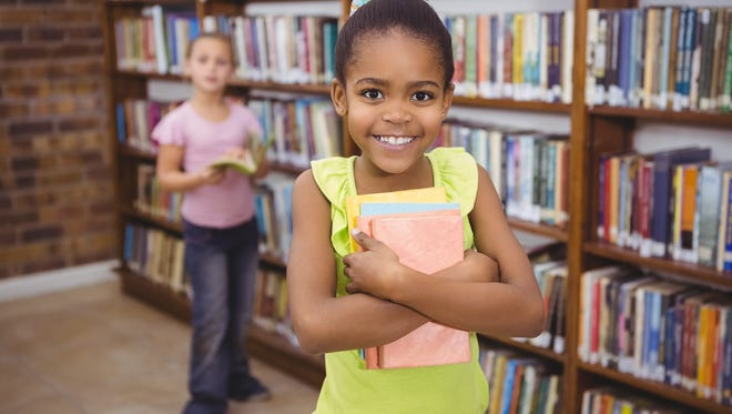 Stock photo: Smiling student holding books.
