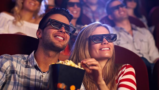Happy couple sitting in movie theater, watching 3D movie, eating popcorn, smiling..
