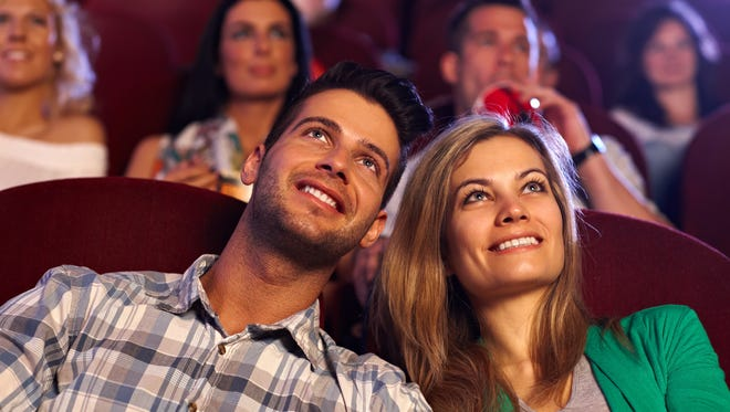 Happy young couple watching movie in cinema, smiling..