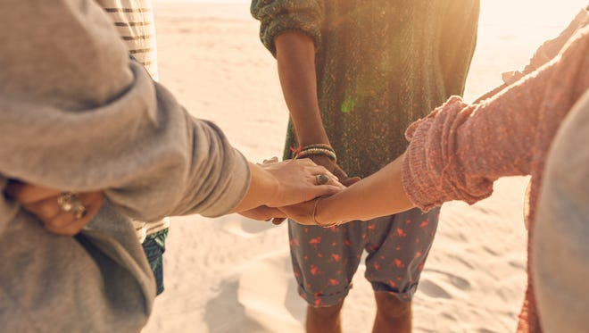 Group of friends stack their hands together. Young men and women standing together at the beach stacking their hands, concept of unity and teamwork.