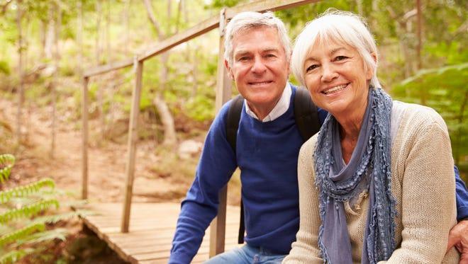 Happy senior couple sitting on a bridge in forest, portrait