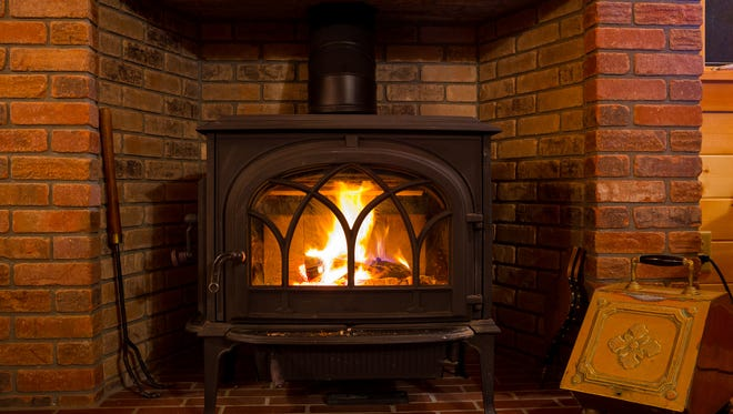 A fire burns in a wood stove. The ash left behind can be used in the garden.
