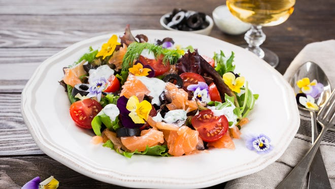 Fresh salad with smoked salmon, black olives, cherry tomatoes and edible flowers combine adventurous flavors.