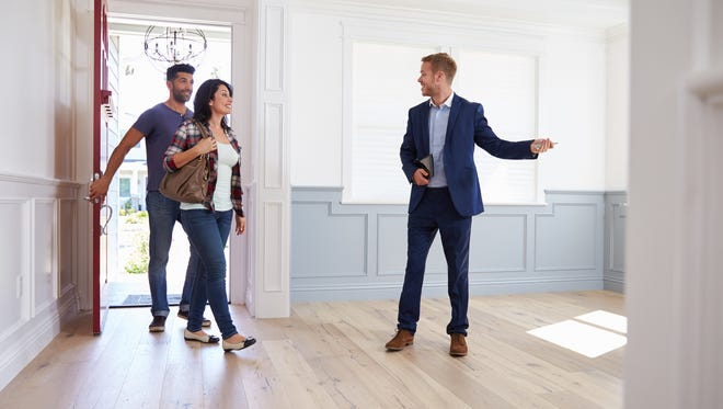 Realtor shows couple around a home for sell during their house hunt